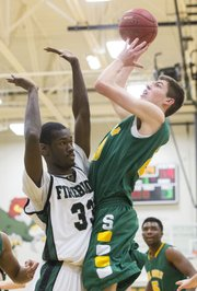 Free State senior Khadre Lane (33) defends a shot by Shawnee Mission South's Hunter Ahrens during their game, Tuesday at FSHS.