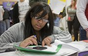 """Lawrence High School junior Tasheana Dixon deducts her mortgage cost from her monthly income at the """"Housing"""" booth Wednesday during the Reality U program at the school."""