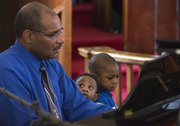 One-year-old Jayvion Lewis, center watches as his grandfather, George Rennels, plays the piano during a worship service at St. Luke AME church, 900 New York St. on Sunday, Feb. 16, 2014. Also pictured is 3-year-old Jeremiah Lewis.