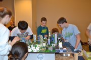 The Southwest Middle School Future City team hurries to reassemble their model city just before their presentation at the national Future City competition in Washington, D.C. Pictured clockwise, from front right, are: Ting Ting Shi; Claire Walther; Jeseung Lee; Quentin Harrington; Paul Loupe; and Brian Myers.