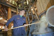 Geoff Deman, head brewer at Free State Brewery, pulls out spent malt from the lauter tun, after straining allowed separation of the liquid from the grain. The liquid, called wort, is then put in a kettle where it is boiled with hops and possibly other ingredients depending on a beer's recipe. Hops add flavor, aroma and bitterness to the beer.