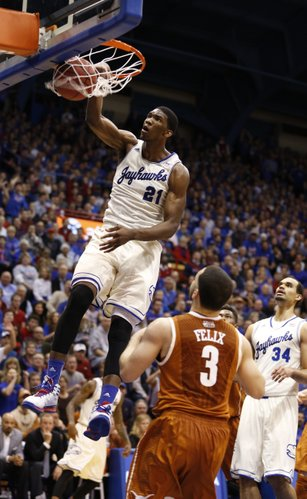 Kansas center Joel Embiid delivers a thunderous dunk before Texas guard Javan Felix during the first half on Saturday, Feb. 22, 2014 at Allen Fieldhouse.