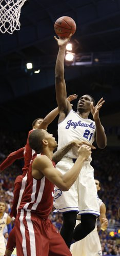 Kansas center Joel Embiid elevates for a shot over Oklahoma forward D.J. Bennett during the second half on Monday, Feb. 24, 2014 at Allen Fieldhouse.