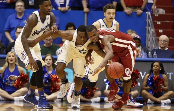 Kansas guard Andrew Wiggins collides with Oklahoma guard Buddy Hield as the two vie for a loose ball during the second half on Monday, Feb. 24, 2014 at Allen Fieldhouse. Also pictured are KU forward Jamari Traylor, left, and guard Brannen Greene.