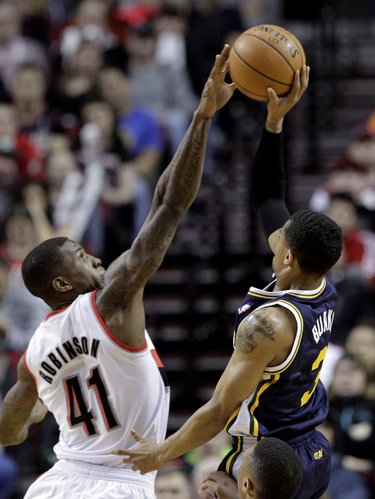 Utah Jazz guard Trey Burke, right, shoots over Portland Trail Blazers forward Thomas Robinson during the first half of an NBA basketball game in Portland, Ore., Friday, Feb. 21, 2014. (AP Photo/Don Ryan)