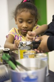 Five-year-old Leah Anderson, of Lawrence, gets some assistance opening cans of food during a cooking class held Tuesday at Just Food, 1000 E. 11th St.