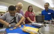 Seven-year-old Trenton Stallworth slices chicken under the watchful eye of his grandmother, Cindy Pippert, both of Lawrence, during a cooking class held Tuesday at Just Food, 1000 E. 11th St. Also pictured are Jessica Wilson and Jahmal Clemons.