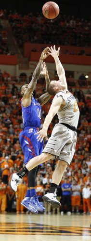 Kansas guard Naadir Tharpe hoists a three over Oklahoma State guard Phil Forte during the first half on Saturday, March 1, 2014 at Gallagher-Iba Arena in Stillwater, Oklahoma.