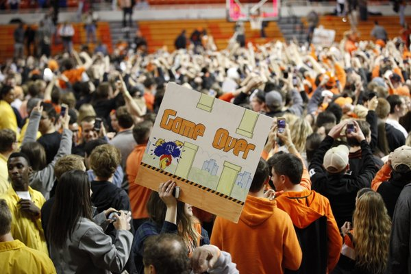 An Oklahoma State fan hoists a sign celebrating the Jayhawks' demise on Saturday, March 1, 2014 at Gallagher-Iba Arena in Stillwater, Oklahoma.