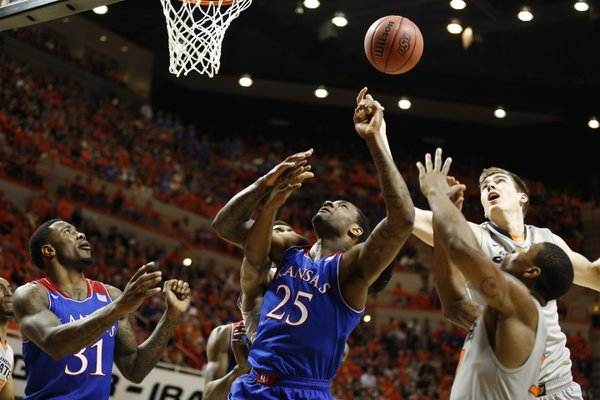 Kansas forward Tarik Black tangles in the paint with Oklahoma State defenders Mason Cox, back right, and Marcus Smart during the second half on Saturday, March 1, 2014 at Gallagher-Iba Arena in Stillwater, Oklahoma.