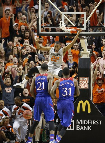 Kansas players Joel Embiid and Jamari Traylor watch as Oklahoma State guard Markel Brown comes down from a dunk during the second half on Saturday, March 1, 2014 at Gallagher-Iba Arena in Stillwater, Oklahoma.