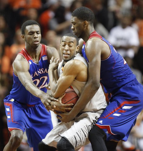 Kansas player Joel Embiid, right, and Andrew Wiggins try to tie up Oklahoma State guard Markel Brown during the second half on Saturday, March 1, 2014 at Gallagher-Iba Arena in Stillwater, Oklahoma.