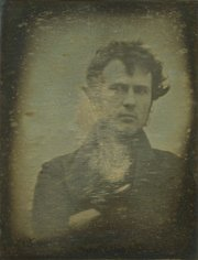 In what is considered one of the earliest self-portraits, Robert Cornelius creates a daguerreotype of a head-and-shoulders photo of himself, facing front, with arms crossed in 1839.