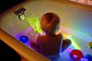 The Kid plays with glow sticks and toys during a rock'n'glow bath session.
