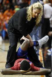 Kansas University men's basketball strength coach Andrea Hudy stretches out Andrew Wiggins, who is most likely to declare his intention to enter the NBA Draft after his freshman season.
