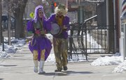 Katie Euliss and Mike West were the first to arrive for the start of the downtown Lawrence Mardi Gras parade in 2014.