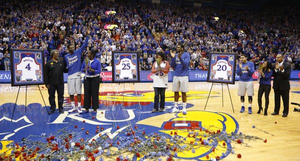 Kansas seniors Justin Wesley, left, Tarik Black and Niko Roberts are applauded by the fieldhouse during a ceremony honoring them with their families prior to tipoff against Texas Tech on Wednesday, March 5, 2014 at Allen Fieldhouse.