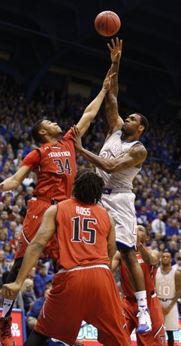Kansas forward Tarik Black hoists a shot over Texas Tech forward Alex Foster during the first half on Wednesday, March 5, 2014 at Allen Fieldhouse.