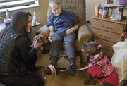 Mike Yoder/Journal-World Photo. Raven Rajani, founder and director of Loving Paws Animal Assisted Therapy, left, visits Marion Counts, center, a resident at Brandon Woods at Alvamar, with her dogs, Brahma, left and therapy dog Shakti, right. The therapy animal teams provide services throughout the community, including visits to community centers, nursing care facilities and schools.