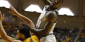 Kansas forward Jamari Traylor loses the ball over West Virginia forward Remi Dibo during the first half on Saturday, March 8, 2014 at WVU Coliseum in Morgantown, West Virginia.