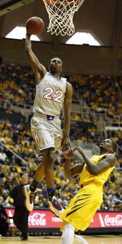 Kansas guard Andrew Wiggins elevates for a dunk over West Virginia guard Eron Harris during the first half on Saturday, March 8, 2014 at WVU Coliseum in Morgantown, West Virginia.