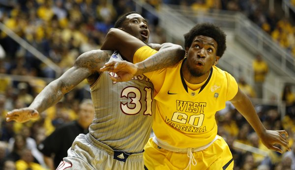 Kansas forward Jamari Traylor and West Virginia forward Brandon Watkins get tangled as they battle for a rebound during the first half on Saturday, March 8, 2014 at WVU Coliseum in Morgantown, West Virginia.