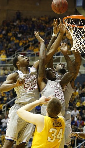 Kansas players Andrew Wiggins, left, Jamari Traylor and Tarik Black, go for a putback bucket over West Virginia forward Kevin Noreen during the second half on Saturday, March 8, 2014 at WVU Coliseum in Morgantown, West Virginia.