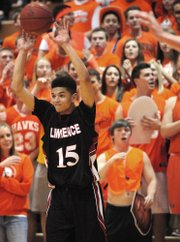Lawrence High's Anthony Bonner ignores the home crowd to get a pass off on Saturday, March 8, 2014, in Olathe.