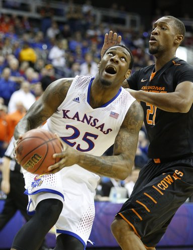 Kansas forward Tarik Black heads to the bucket under Oklahoma State forward Kamari Murphy during the first half on Thursday, March 13, 2014 at Sprint Center in Kansas City, Missouri.
