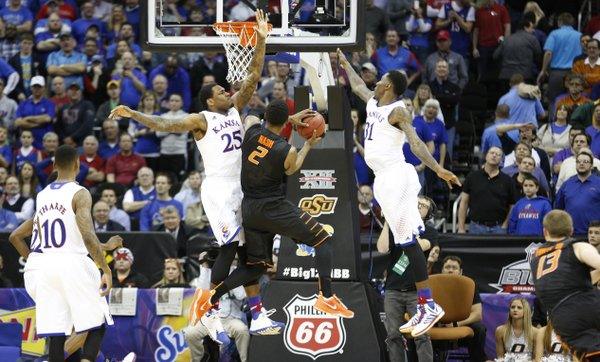 Kansas defenders Tarik Black, left, and Jamari Traylor defend against a final shot from Oklahoma State forward Le'Bryan Nash during overtime on Thursday, March 13, 2014 at Sprint Center in Kansas City, Missouri.