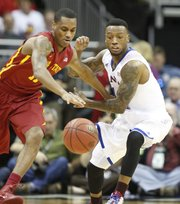 Kansas guard Naadir Tharpe looks to strip the ball from Iowa State guard Monte Morris during the first half on Friday, March 14, 2014 at Sprint Center in Kansas City, Missouri.