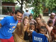 Madeline Heeren and Aqmar Rahman, law students at Kansas University, give a T-shirt to a child in a slum on the outskirts of Dhaka, Bangladesh last summer. After their trip to Bangladesh, Heeren and Rahman co-founded United Across Borders, a nonprofit organization that aims to provide clothing and blankets to the impoverished in developing countries.