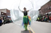 A super-hero participant walking along with the VFW float, spreads her wings on Massachusetts St. Monday, March 17, 2014 during the St. Patrick's Day Parade.