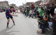 A member of the Kansas Jayhawk Rugby Club tosses a ball to a boy in the crowd Monday, March 17, 2014 during the St. Patrick's Day Parade.