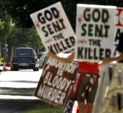 In this June 6, 2009 file photo, protesters from Rev. Fred Phelps' Westboro Baptist Church demonstrate during funeral services for Dr. George Tiller at College Hill United Methodist Church in Wichita, Kan. In an 8-1 ruling, the U.S. Supreme Court ruled the group's protests were protected by the First Amendment. The father of a Marine killed in Iraq sued after they picketed his son's 2006 funeral service.