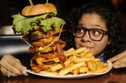 "Richard Gwin/Journal World Photo.Journal World reporter Nadia Imafidon looks to take on the challenge of eating the ""Everest Challenge"",  at the 23rd Street Brewery."