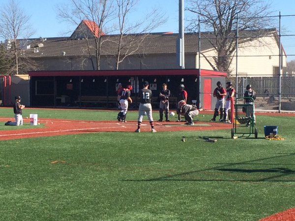 Lawrence High catchers practice fielding pitches in the dirt during drills.