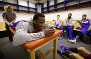 Kansas guard Wayne Selden smiles while thumbing through an iPhone as strength and conditioning coach Andrea Hudy works on this calves in the team locker room during a day of press conferences and practices at the Scottrade Center in St. Louis on Thursday, March 20, 2014.
