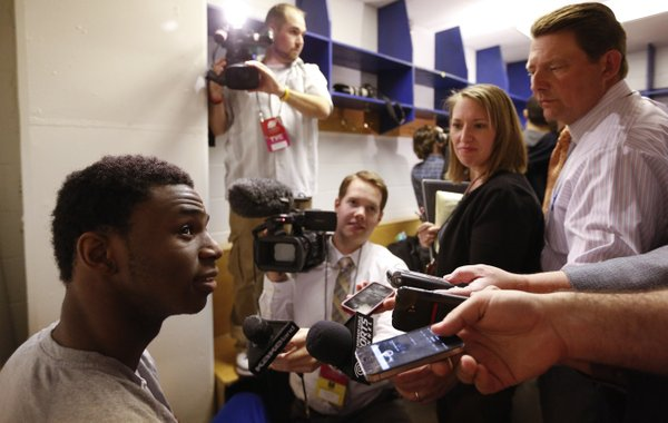 Kansas guard Andrew Wiggins grins as he answers questions from media members in the team locker room during a day of press conferences and practices at the Scottrade Center in St. Louis on Thursday, March 20, 2014.