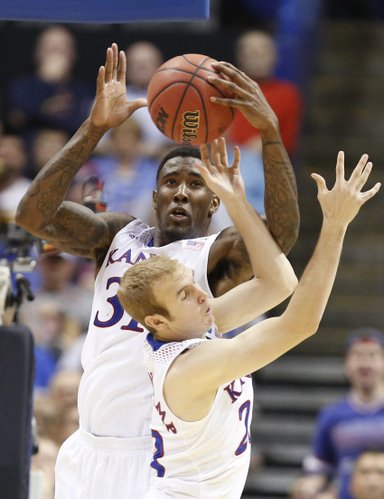 Kansas forward Jamari Traylor grabs a rebound over teammate Conner Frankamp during the second half on Friday, March 21, 2014 at Scottrade Center in St. Louis.