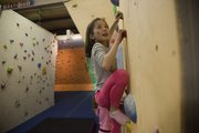 Jopsephine Vee, 8, works her way up the climbing wall at CrossFit Lawrence.
