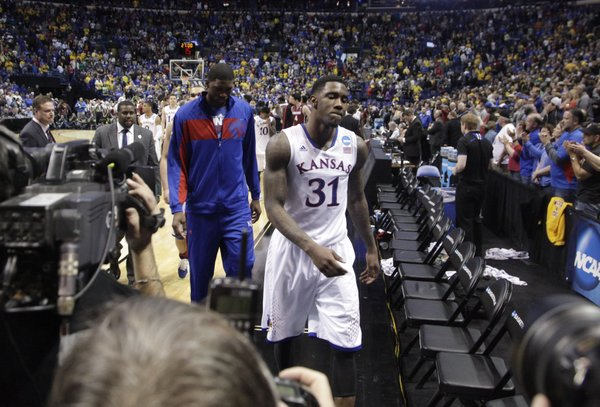 Kansas forward Jamari Traylor and center Joel Embiid walk off the court following the Jayhawks 60-57 loss to Stanford, Sunday March 23, 2014, at the Scottrade Center in St. Louis.