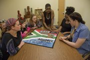 "From left, Sylvan Mitchell, 15 of Vinland, Teagan Harmon, 9 of Lecompton, and Kearston Mohney, 16 of Lawrence, listen to Marla Jackson talk about a quilt called ""The Mandela Project"" at Jackson&squot;s studio at Independence Inc. on Saturday March 22, 2014."