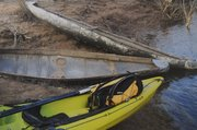A plastic kayak rests next to two steel bomb casings.