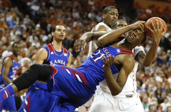 Kansas forward Joel Embiid is sent to the floor by Texas center Cameron Ridley while battling for a rebound during the first half on Saturday, Feb. 1, 2014 at Erwin Center in Austin, Texas.