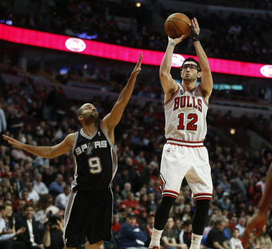 Chicago Bulls shooting guard Kirk Hinrich (12) shoots past San Antonio Spurs point guard Tony Parker (9) during the second half of an NBA basketball game on Tuesday, March 11, 2014, in Chicago. The San Antonio Spurs defeated The Chicago Bulls 104-96. (AP Photo/Andrew A. Nelles)