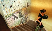 Free State Brewing Co. server Elizabeth Cunningham makes her way down the stairs past a mosaic created by Lawrence artist Lora Jost.