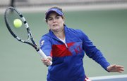 Kansas University's Caroline Henderson reaches for a return during a match against Oklahoma State on Friday, March 28, 2014 at Jayhawk Tennis Center.