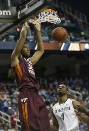Virginia Tech's Trevor Thompson (32) dunks as Miami's Raphael Akpejiori watches in this photo from March 12, in Greensboro, N.C. Thompson has been granted his release and has been contacted by Kansas University coaches, according to a published report.