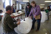 From left, Scott Luebbering, Chanute, of Engineers Without Borders, helps Carl and Irma Ward, Clinton, put together their rain barrel Saturday at the Douglas County Fairgrounds. They were part of about two dozen people participating in a rain barrel workshop commemorating International World Water Day.